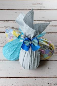 Uova di pasqua di cioccolato confezionate con tessuti colorati e fiocchi su un tavolo di legno bianco.