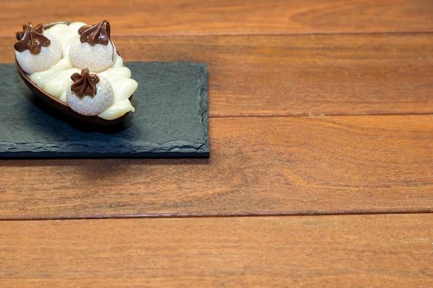 Uova di pasqua di cioccolato in cima alla pietra nera con fondo in legno