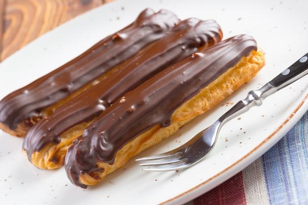 Eclairs al cioccolato sulla zolla bianca sulla tavola di legno