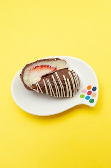 Uovo di cioccolato (uovo di pasqua) cocco farcito con fragole tagliate a metà su un piatto. isolato su sfondo giallo.