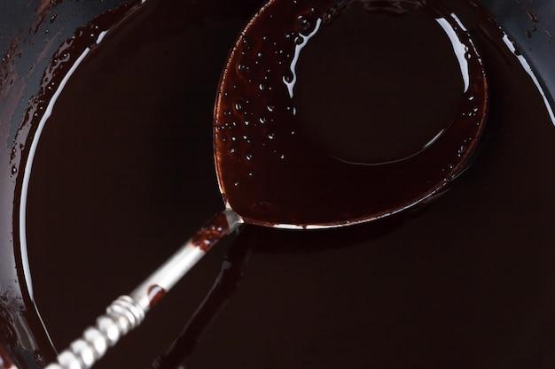 Cucchiaio d'argento riempito di cioccolato in una padella