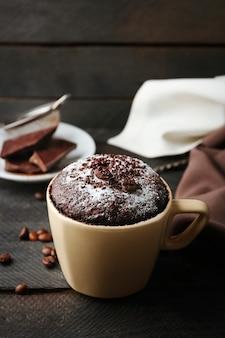 Torta al cioccolato fondente in tazza su legno