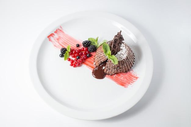Fondente al cioccolato con frutti di bosco e menta sulla piastra bianca.