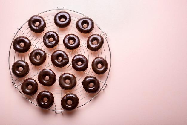 Ciambelle glassate al cioccolato su una griglia di raffreddamento. fare ciambelle al cioccolato