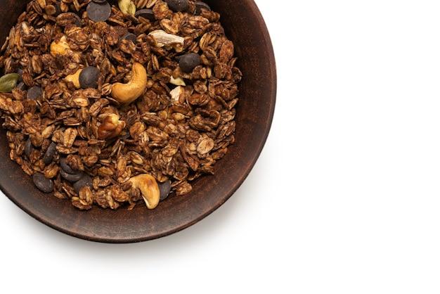 Cereali di muesli al cioccolato con noci in uno sfondo di ciotola. isolato su sfondo bianco.