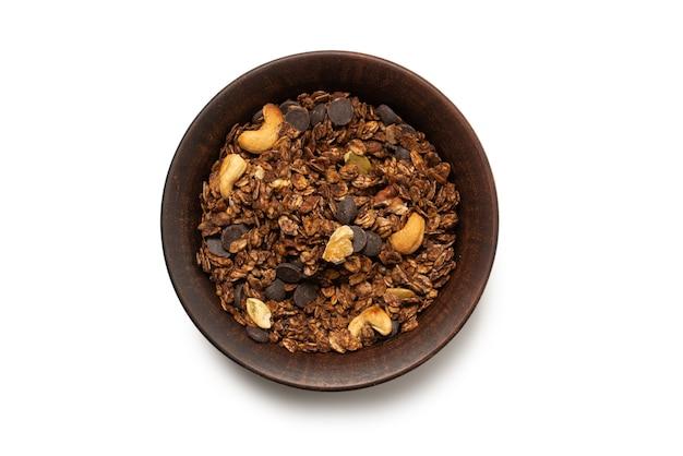 Cereali muesli al cioccolato con noci in una superficie della ciotola. isolato su sfondo bianco.