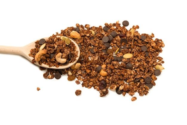 Cereali di muesli al cioccolato con noci in un cucchiaio di legno. isolato su sfondo bianco.