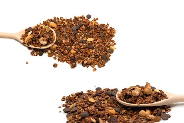 Cereali di muesli al cioccolato con noci in un cucchiaio di legno. isolato su sfondo bianco. Foto Premium