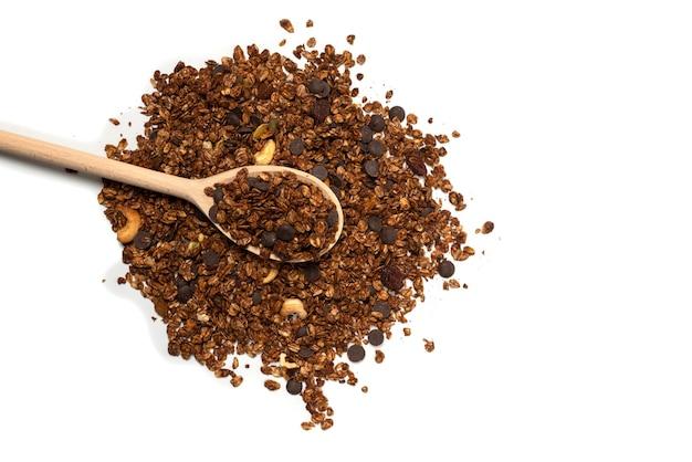 Cereali muesli al cioccolato con noci in un cucchiaio di legno. isolato su bianco.