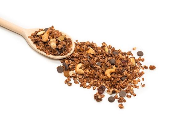 Cereali di muesli al cioccolato con noci in un cucchiaio di legno. isolato su bianco.