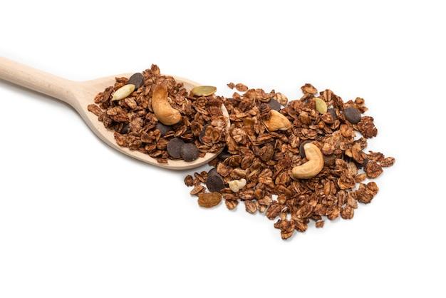 Cereali di muesli al cioccolato con noci in un cucchiaio di legno. isolato su bianco