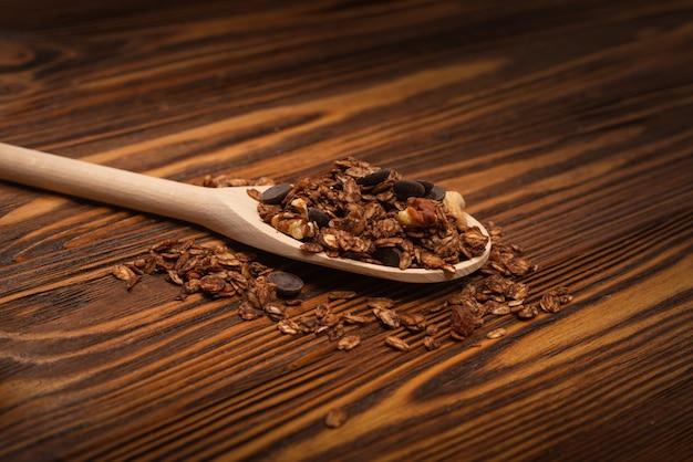 Cereali di muesli al cioccolato con noci in un cucchiaio di legno. su una superficie di legno.