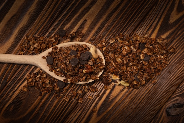 Cereali muesli al cioccolato con noci in un cucchiaio di legno. su un tavolo di legno.