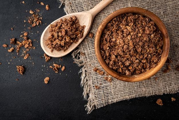 Muesli al cioccolato in ciotola di legno su sfondo nero.