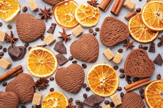 Biscotti al cioccolato cuore, arance cannella e spezie piccanti su un tavolo grigio, vista dall'alto, primi piani.