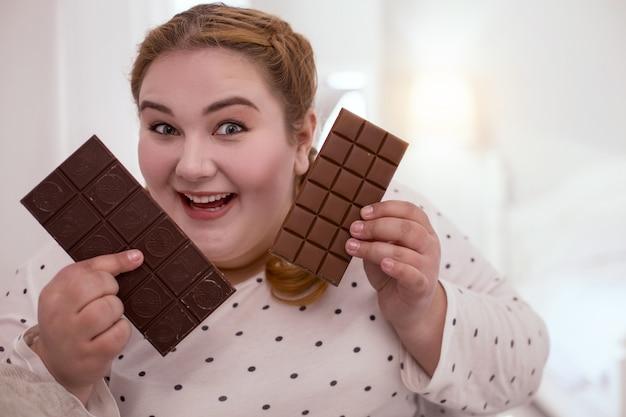 Paradiso del cioccolato. donna dai capelli rossi soddisfatta che gode del gusto del cioccolato mentre ne tiene due barre nelle sue mani