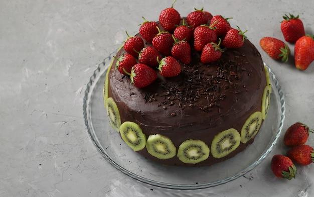 Torta fatta in casa al cioccolato decorata con fragole e kiwi situati su sfondo grigio cemento, formato orizzontale, primo piano, spazio copia Foto Premium