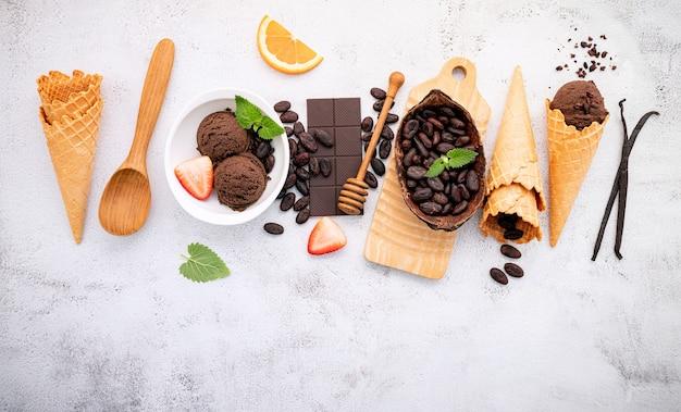 Gusti di gelato al cioccolato nella configurazione della ciotola su pietra bianca.
