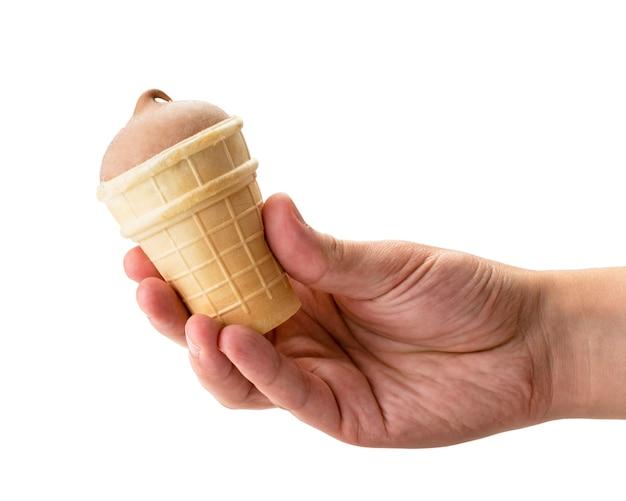 Gelato al cioccolato in una tazza della cialda che tiene la mano di un uomo su bianco