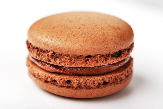 Biscotti dei maccheroni del cioccolato su un fondo bianco con materiale da otturazione marrone, isolato.