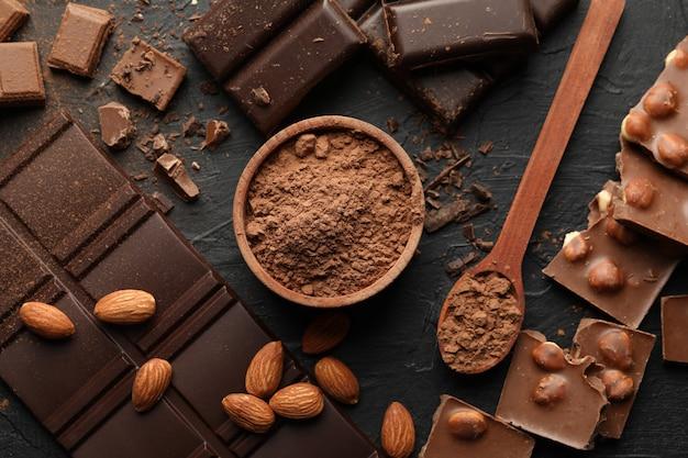 Cioccolato, cioccolato fuso e mandorle su sfondo nero
