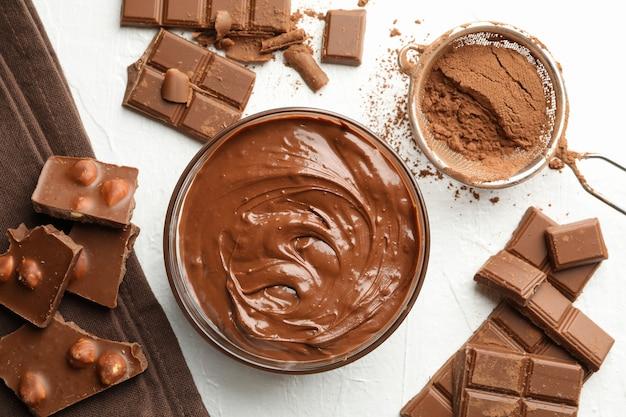 Cioccolato, cioccolato fuso e polvere su bianco