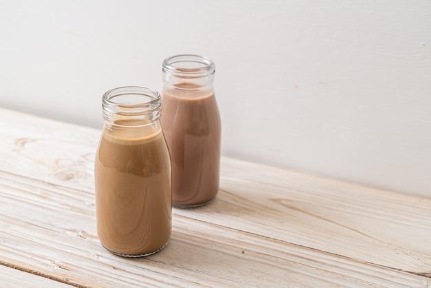 Latte al cioccolato e caffè con latte in bottiglia su uno sfondo di legno