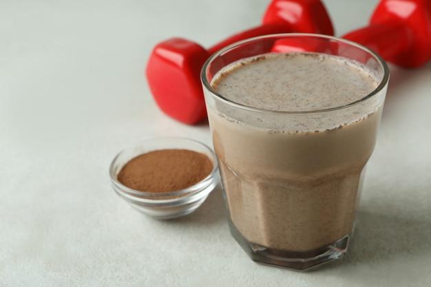 Frappè al cioccolato, cioccolato in polvere e manubri sul tavolo bianco strutturato
