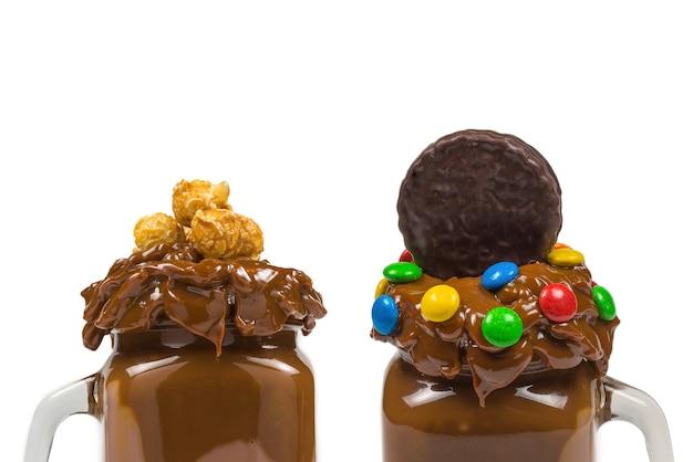 Frappè al cioccolato con panna montata, biscotti, waffle, servito in un barattolo di vetro. dolce frullato
