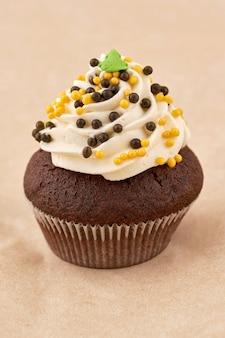Torta di muffin al cioccolato con crema di marshmallow. primo piano su sfondo chiaro, telaio verticale