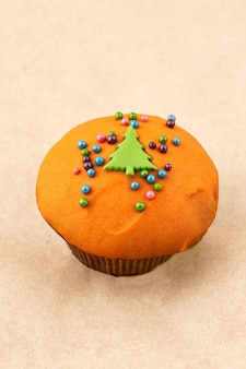 Muffin al cioccolato con glassa all'arancia e decorazioni natalizie. primo piano su sfondo chiaro, telaio verticale
