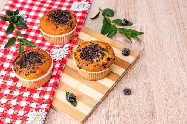 Muffin al cioccolato e muffin alle noci, prodotti da forno fatti in casa su sfondo scuro.