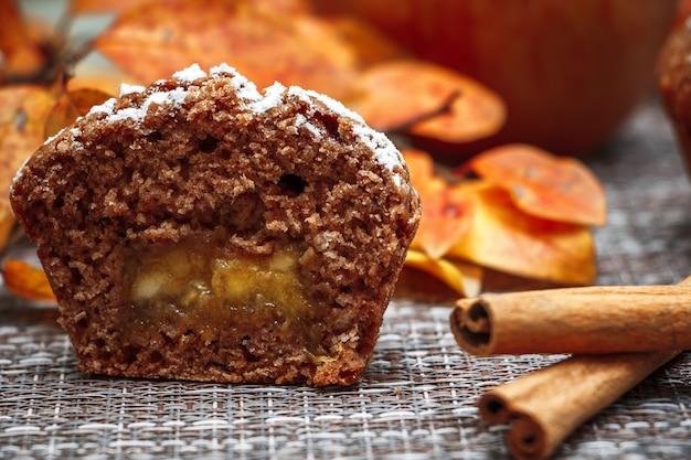 Muffin al cioccolato con ripieno di mele su foglie autunnali e cannella