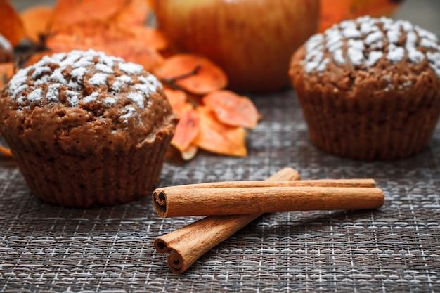 Muffin al cioccolato con ripieno di mele su uno sfondo di foglie autunnali e cannella