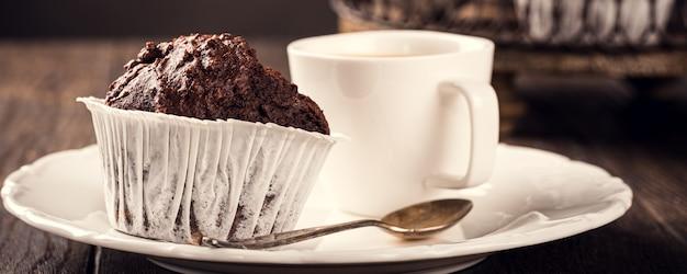 Muffin al cioccolato con banana in bicchieri di carta bianca su superficie di legno scuro. concetto di cibo per feste. banner