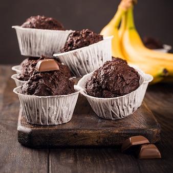 Muffin al cioccolato con banana in bicchieri di carta bianca su superficie di legno scuro. concetto di cibo per feste