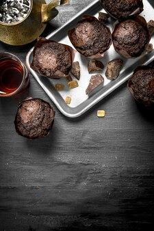 Muffin al cioccolato con tè fresco sulla lavagna nera.