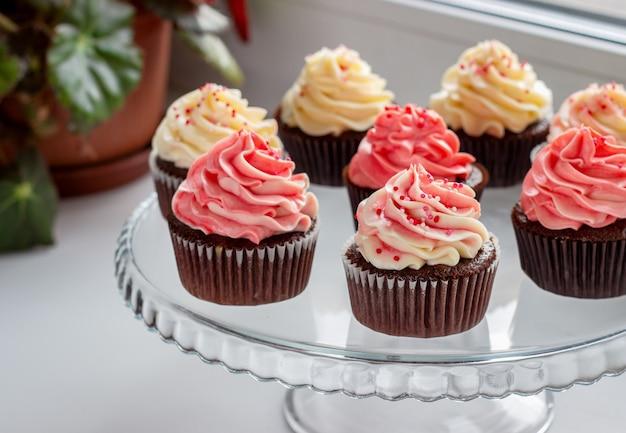 Muffin al cioccolato con un cappello di crema rosa e bianca
