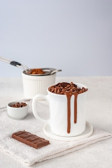 Torta al cioccolato in tazza bianca con gocce di cioccolato e polvere di coca