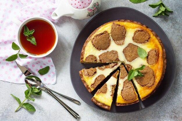 Cheesecake al cioccolato new york e tazza da tè alla menta su sfondo di cemento vista dall'alto sfondo piatto disteso