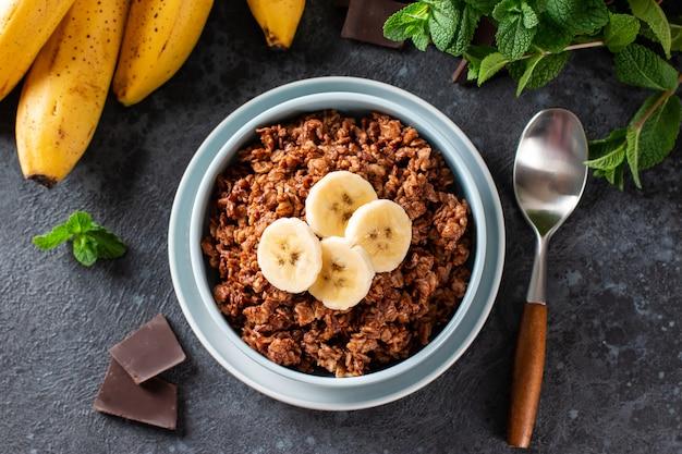 Farina d'avena al cioccolato con banana - sana colazione vegetariana su sfondo grigio, vista dall'alto. disposizione piatta, copia spazio