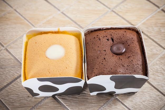 Torta al cioccolato, arancia sulla tazza di mucca.