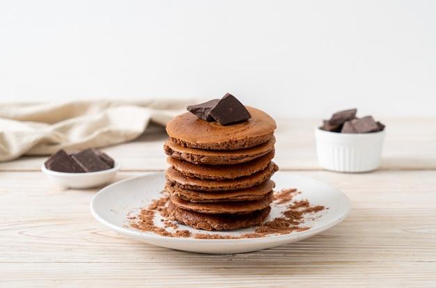 Pila di frittelle al cioccolato con cioccolato in polvere