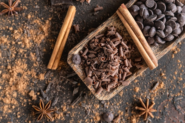 Scaglie e gocce di cioccolato con cacao in polvere e spezie concetto di cibo dolce