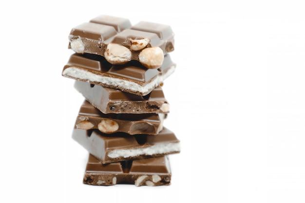 I pezzi di cioccolato di diversi tipi impilati su sfondo bianco.