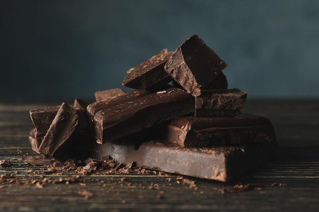 Pezzi del cioccolato su fondo di legno, fine su
