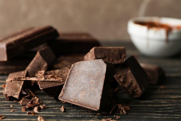 Pezzi del cioccolato su di legno, vicino
