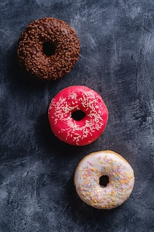 Ciambelle al cioccolato, rosa e vaniglia con un pizzico in fila, dolce cibo da dessert glassato sul tavolo testurizzato di cemento scuro, vista dall'alto