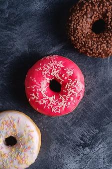 Ciambelle al cioccolato, rosa e vaniglia con granelli in fila, dolce cibo da dessert glassato su cemento scuro strutturato