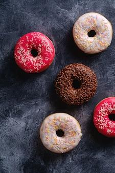 Ciambelle al cioccolato, rosa e vaniglia con spruzza, dolce cibo da dessert glassato su sfondo strutturato in cemento scuro, vista dall'alto